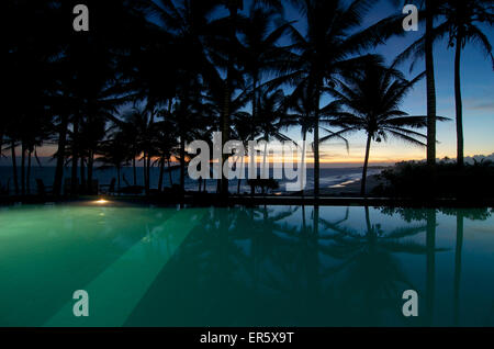 Pool under palm trees with sea view at sunset, Turtle Bay Hotel, Tangalle, South coast, Sri Lanka - Stock Photo