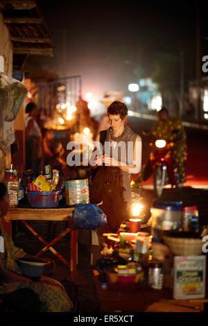 Woman at a night market, Ouidah, Atlantique Department, Benin - Stock Photo
