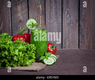 Fresh green smoothie with cucumber, green salad leaves, tomato and red capsicum at wooden background - Stock Photo