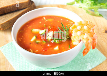 delicious tasty cold vegetable tomato soup gazpacho with shrimps (prawns) and rosemary in white bowl on wooden background, - Stock Photo