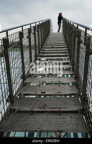 Man ascends a metal bridge over a glass roof at the Warsaw University Library garden, designed by Irena Bajerska - Stock Photo