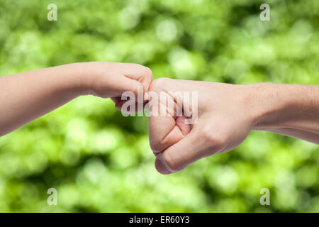 father and son punching fists/hands for agreement on green nature background - Stock Photo