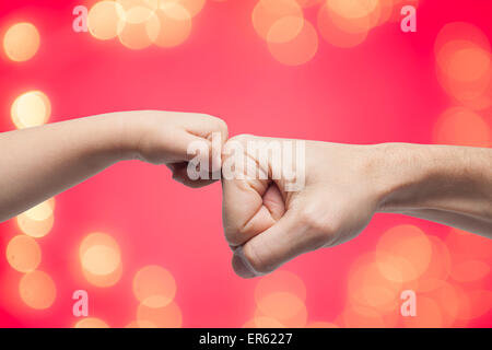 father and son punching fists for agreement on yellow christmas lights and red background. - Stock Photo
