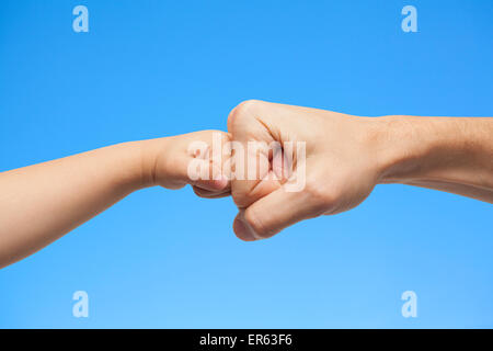 father and son punching fists/hands for agreement on blue sky background. - Stock Photo