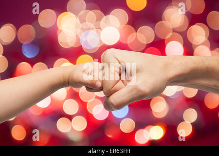 father and son punching fists for agreement on multicolored christmas lights background. - Stock Photo