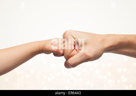 father and son punching fists for agreement on beautiful christmas lights background. - Stock Photo