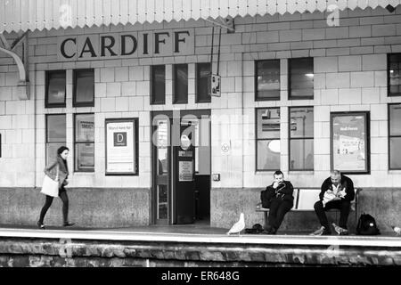 Passengers waiting at Cardiff Central Station, Wales UK in May Cardiff train station  - black and white monochrome - Stock Photo