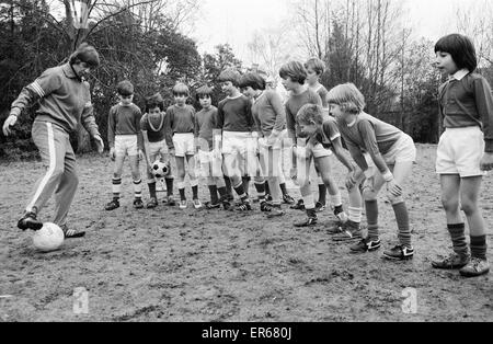 Queens Park Rangers footballer Don Masson coaching children to play football at the Our Lady of Angels School in - Stock Photo