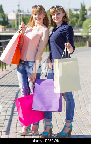Young twins girls have fun holding their shopping bags. Two women shopping at summer day in city - Stock Photo