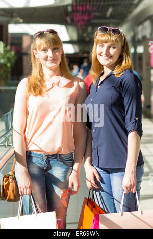 Young twins girls have fun holding their shopping bags. Two caucasian sisters smiling at the shopping mall - Stock Photo