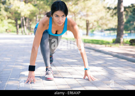 Sporty woman runner in start position outdoors in park - Stock Photo