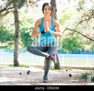 Happy sporty woman doing yoga exercises oudoors in park and looking at camera - Stock Photo