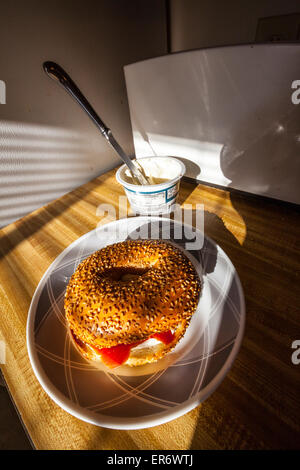 A sesame seed bagel with cream cheese and smoked salmon in the early morning light streaming through a window. - Stock Photo