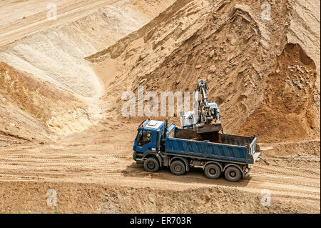 Digger fills a truck with sand at brown coal mining Garzweiler in North Rhine Westphalia, Germany. - Stock Photo