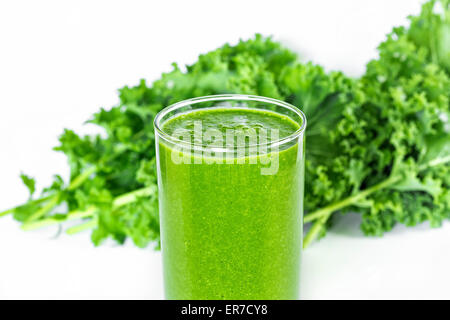 Green smoothie with kale in background. - Stock Photo