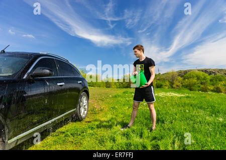 Young Man Washing Black Luxury Vehicle in Grassy Green Field on Bright Sunny Day with Blue Sky, Tossing Bucket of - Stock Photo