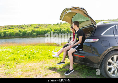 Young Couple Sitting on Rear Tailgate Bumper of SUV Vehicle Parked in Green Field by River on Sunny Day, Enjoying - Stock Photo