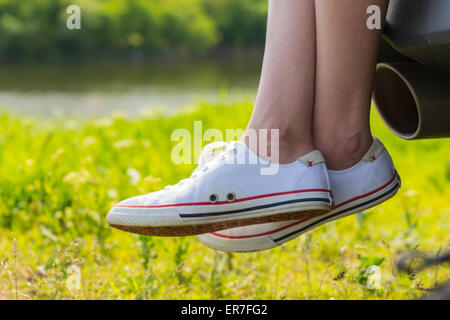 Close Up of Woman Wearing Sneakers Sitting with Crossed Ankles on Rear Tailgate of Vehicle with View of Exhaust - Stock Photo