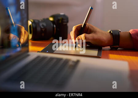 Photographer drawing and retouching image on laptop computer, using a digital tablet and stylus pen. Closeup of - Stock Photo