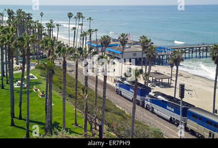 Passengers on an Amtrak train enjoy great views of the Pacific Ocean as they speed past the San Clemente pier in - Stock Photo