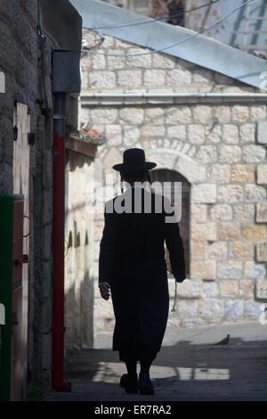 JERUSALEM, ISR - MAR 19 2015:Orthodox Jewish man walks in old street in Jerusalem, Israel.About 30 percent of the - Stock Photo
