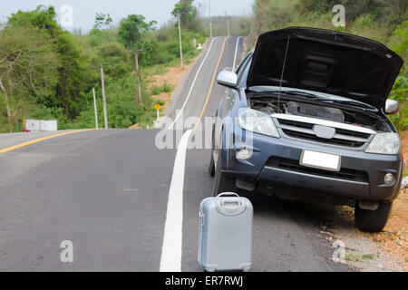 Broken down car on the side of a road - Stock Photo