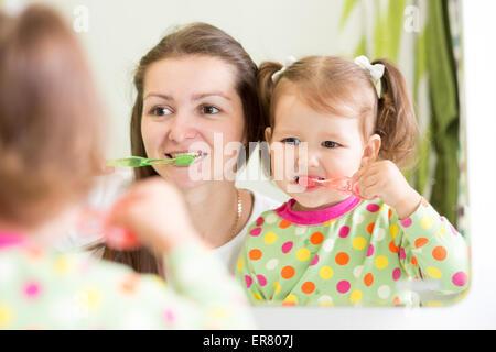 mom teaching daughter child teeth brushing in bathroom - Stock Photo