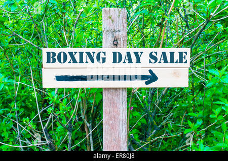 BOXING DAY SALE written on Directional wooden sign with arrow pointing to the right against green leaves background. - Stock Photo