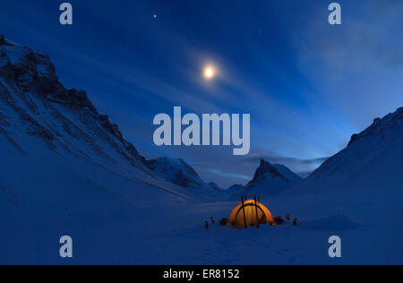 Tent in the mountains on a winter night in Lapland. - Stock Photo