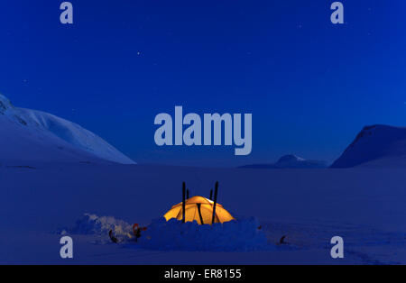 Tent at night in the snow covered mountains of Lapland, Sweden. - Stock Photo