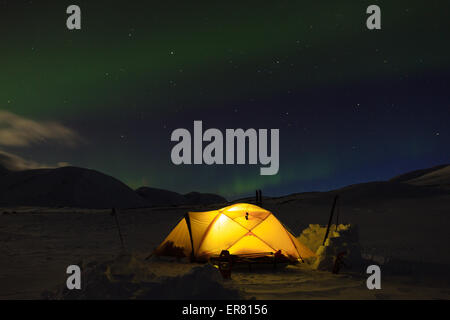 Aurora borealis, Northern Lights, over a tent in the snow in Swedish Lapland. - Stock Photo