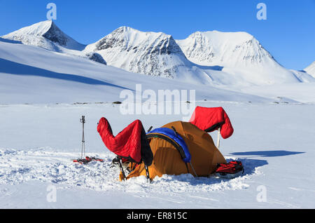 Sleeping bags drying in the sun at a winter campsite in Lapland, Sweden. - Stock Photo