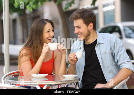 Happy couple or friends flirting talking and drinking in a restaurant terrace - Stock Photo