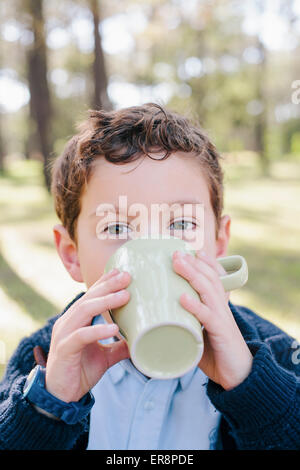 Close-up portrait of boy drinking coffee in forest - Stock Photo