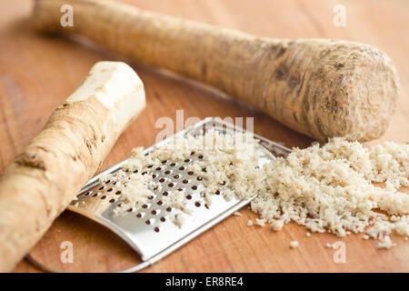 grated horseradish root on kitchen table - Stock Photo
