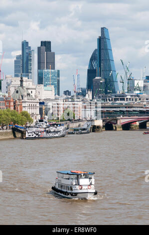 Office buildings on the London City skyline seen from Waterloo Bridge with a tourist pleasure cruise boat on the - Stock Photo