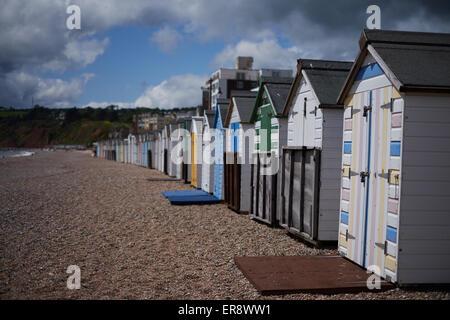 A row of colorful beach huts on a pebble beach in Seaton, Devon - Stock Photo