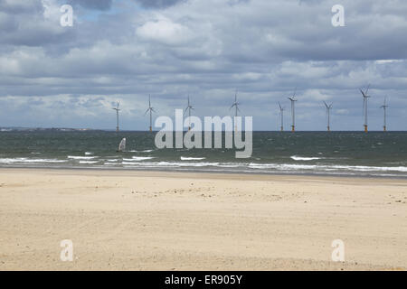 A windsurfer passes the Teeside wind farm photographed from Redcar beach. 27 offshore turbines in the estuary of - Stock Photo