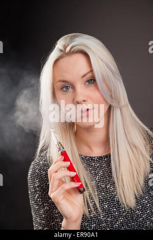 Young woman holding a personal vaporizer. - Stock Photo