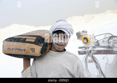 Minya, Egypt. 28th May, 2015. An Egyptian worker carrying packed cement poses on a limestone quarry at the village - Stock Photo