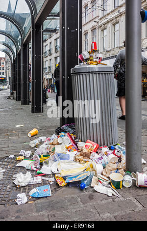 Overfull garbage can with piled up household refuse due to strike by waste processing firm at tramstop in city - Stock Photo