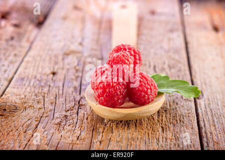 fresh berries in wooden spoon on wooden table - Stock Photo