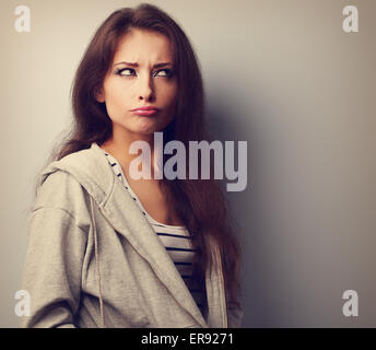 Grimacing fun young woman thinking and looking fun. Vintage portrait - Stock Photo