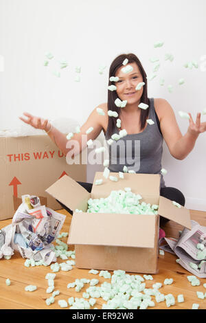 Woman sitting on the floor throwing packing material in the air. - Stock Photo