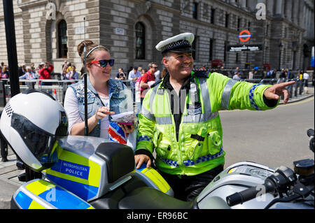 A male traffic police officer in bright yellow jacket with high powered motorbike talking to one young woman, London, - Stock Photo