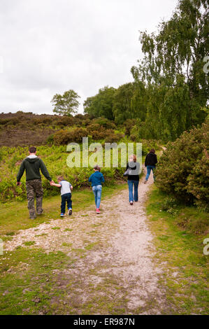 Rear View Of A family Walking Along A Track Together Through The Countryside - Stock Photo