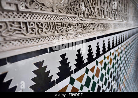 Close up of arabic wall carving and tilework at Alcazar palace Seville Andalusia - Stock Photo