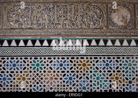 Close up of arabic wall carving and tiles at Alcazar palace Seville Andalusia - Stock Photo