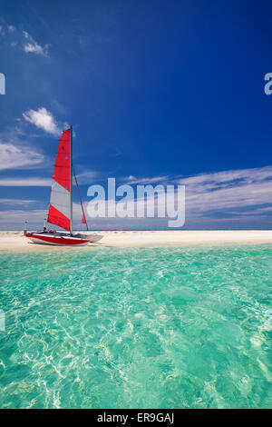 Sailing boat with red sail on beach of deserted tropical island - Stock Photo