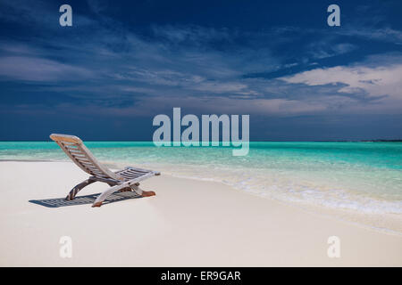 Beach view of amazing water in Maldives - empty chair on sand - Stock Photo